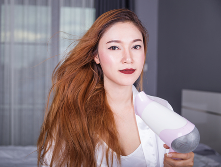 woman using hair dryer in the bedroom Stock Photo