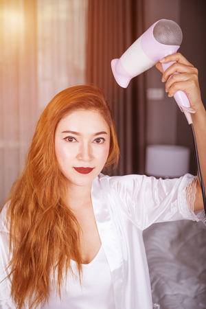 woman using hair dryer in the bedroom with soft light