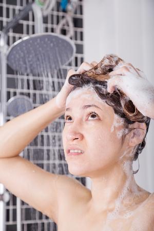 不幸な女性のシャンプーやシャワーで頭を洗う