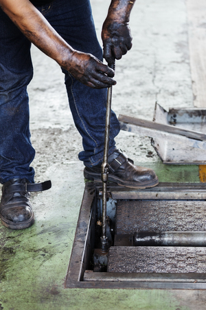 hand of repairman during maintenance work of machine