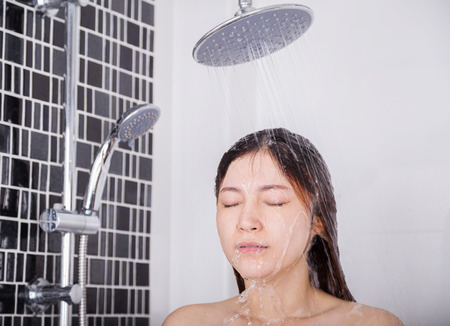 Woman is washing her hair and face by rain shower head