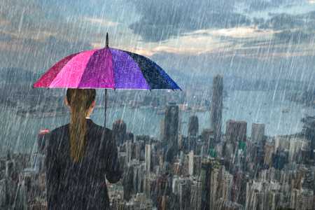 business woman holding multicolored umbrella with falling rain at Hong Kong city background
