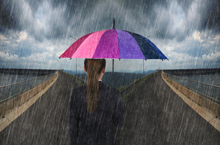 spliting: business woman holding multicolored umbrella with falling rain on cross road spliting in two way