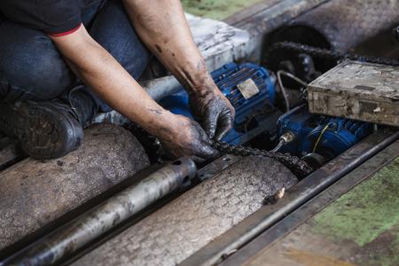 Main de réparateur lors des travaux de maintenance de la chaîne