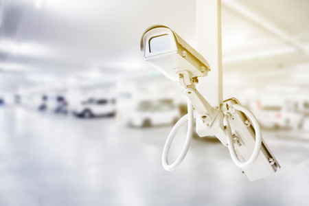 CCTV security camera with blurred car parking background Stock Photo