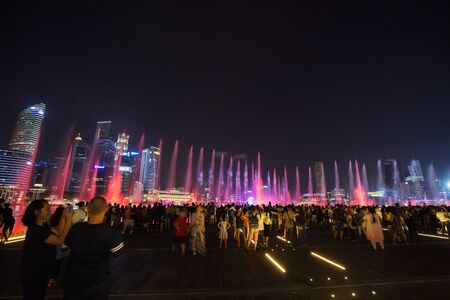 SINGAPORE - AUG 19, 2017 :  Tourists visit SPECTRA � LIGHT & WATER SHOW at Marina bay sands front in Singapore Editorial