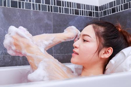 woman washing elbow with pink sponge in bathtub in the bathroom