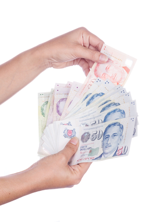 hand with Singapore banknotes dollars (SGD) isolated on a white background