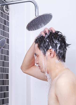 man are taking a rain shower and washing hair in the bathroom Stock Photo