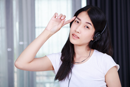 woman in headphones listening to music from smartphone with the window background