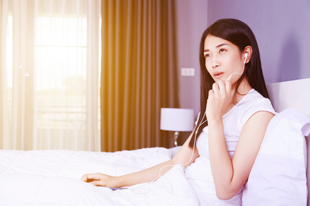 woman using earphone device on mobile phone on bed in the bedroom Stock Photo