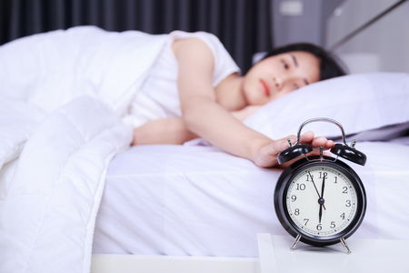 woman sleeping on bed and rise hand to turn off alarm clock in the bedroom