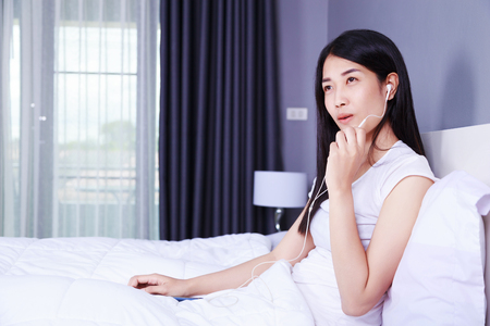 handsfree telephone: woman using earphone device on mobile phone on bed in the bedroom Stock Photo