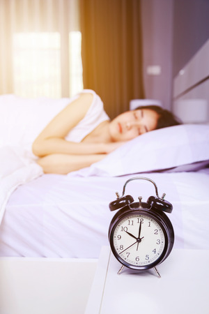 alarm clock on table and woman sleeping on bed in the bedroom