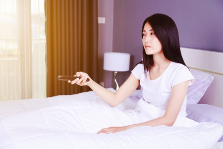 woman watching tv with remote on bed in the bedroom