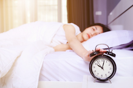 woman sleeping on bed and rise hand to turn off alarm clock in the bedroom Imagens - 88628987