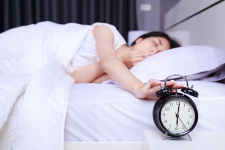 woman yawing on bed and rise hand to turn off alarm clock in the bedroom Banco de Imagens