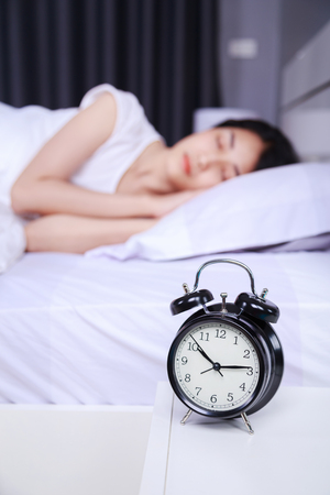 alarm clock on table and woman sleeping on bed in the bedroom Imagens - 88572547