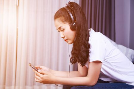 young woman listening to music in headphones with moblie on sofa at home Stock Photo