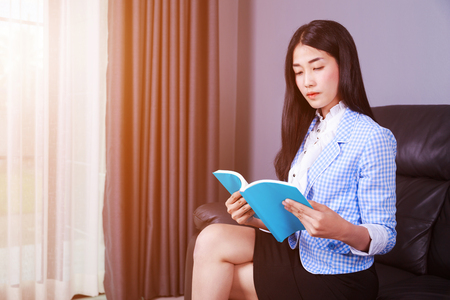 young business woman rests at the sofa and reading a book