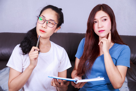 two young woman thinking with a book on sofa in living room at home