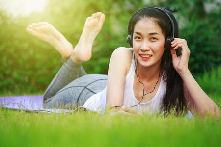 Giovane donna che ascolta la musica con le cuffie e che pone su un campo di erba