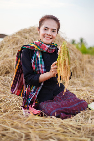 Farmer woman holding a rice with the straw in field, Thailand