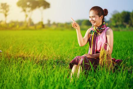 happy farmer woman sitting in green rice filed, Thailand