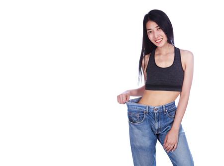 vrouw toont haar gewichtsverlies en het dragen van haar oude spijkerbroek geïsoleerd op een witte achtergrond