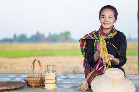 farmer woman holding rice and sitting in cottage at rice field, Thailand
