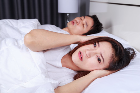 annoyed wife blocking her ears from noise of husband snoring in the bedroom  Stock Photo