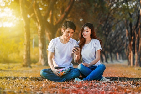 young couple listening music from mobile with headphone in the park