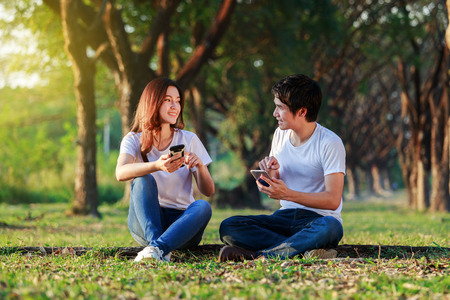 couple using mobile phone and talking in the park