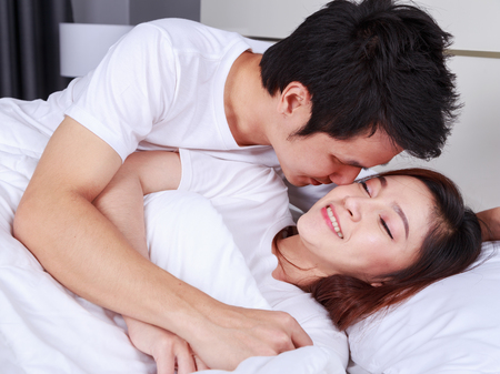 young man is kissing his beautiful smiling wife in cheek on bed Foto de archivo