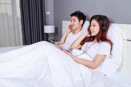 young couple listening music from mobile with headphone on bed