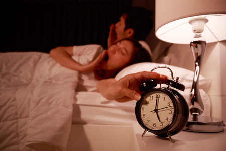 sleepy young couple in bed with extending hand to alarm clock in the morning