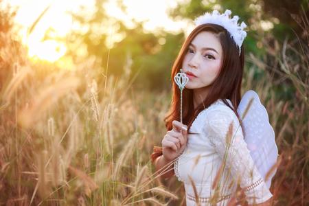 beautiful angel woman in a grass field with sunlight Stock fotó