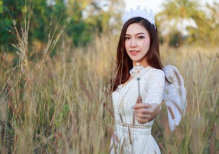 beautiful angel woman in a grass field  스톡 콘텐츠