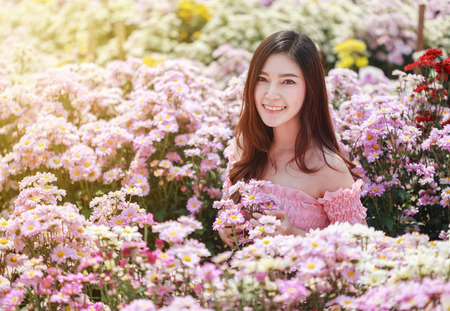 beautiful woman in colorful chrysanthemum glower garden  Archivio Fotografico