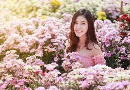 beautiful woman in colorful chrysanthemum glower garden  Standard-Bild