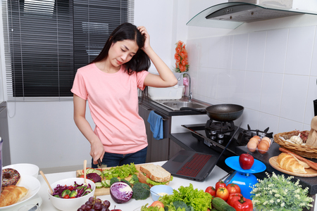 depressed young woman cooking in kitchen room