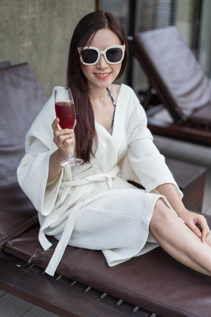 woman clothed bathrobe sitting on deckchair in swimming pool
