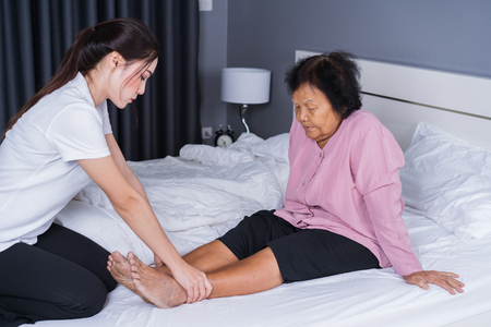 woman hands doing massage on old woman pain legs in a bed