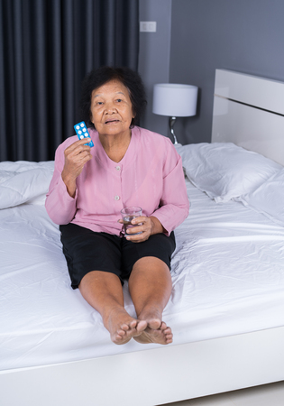 senior woman taking pill with glass of water in a bed