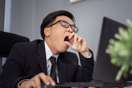 tired young businessman using laptop and yawning