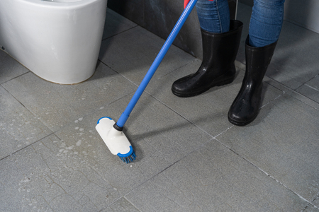 hand using brush to cleaning the tile in the bathroom