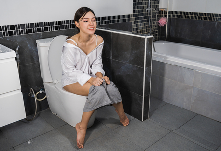 happy young woman sitting on a toilet