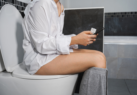 A woman using mobile phone and sitting on the toilet