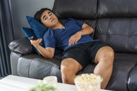 young bored man watching tv and sitting on sofa in the living room Standard-Bild