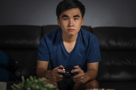 young man playing video game with joystick in the living room at night